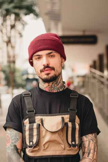 tattooed man in black crew neck t shirt and red knit beanie